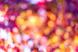 Autumn natural bokeh for background. Defocused abstract autumnal backdrop in yellow, red, orange and purple tones. Copy space. Space for text