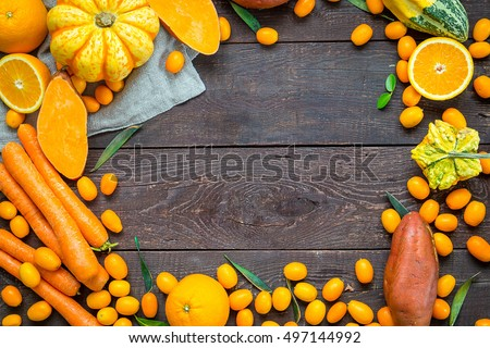 Autumn Nature Concept, Orange Vegetables and Fruits on Dark Wooden Background with Free Space for text, Thanksgiving Dinner, Top View