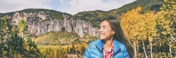 Autumn nature hiker woman walking in Canadian forest nature. Canada fall travel lifestyle, Asian girl smiling enjoying weather. Banner panorama.