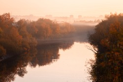 Autumn Omsk city in fog. Om river and autumn orange forests