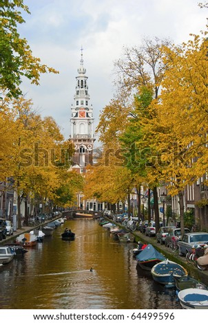 Autumn on a canal in Amsterdam with clock tower in background