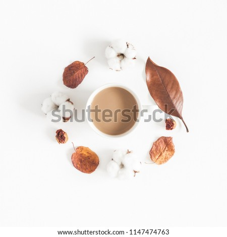 Autumn or winter composition. Cup of coffee, dried autumn leaves, cotton flowers on white background. Flat lay, top view, square
