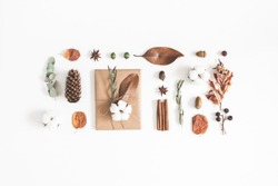 Autumn or winter composition. Gift, dried autumn leaves, cotton flowers on white background. Flat lay, top view