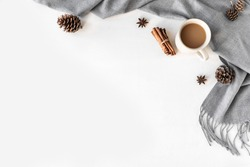 Autumn or winter cozy composition with gray warm blanket and cup of coffee. Seasonal coziness with soft plaid, coffee, cinnamon and cones. Cozy home and hygge concept on white background, copy space.