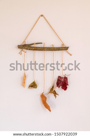 Autumn or winter craft. Fall leaves hanging on wooden stick on grey wall as decoration of interior with copy space.