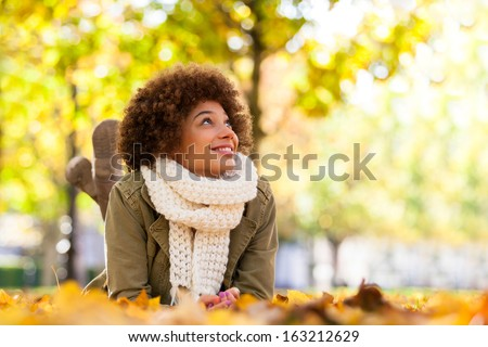Autumn outdoor portrait of beautiful African American young woman lying down - Black people #163212629