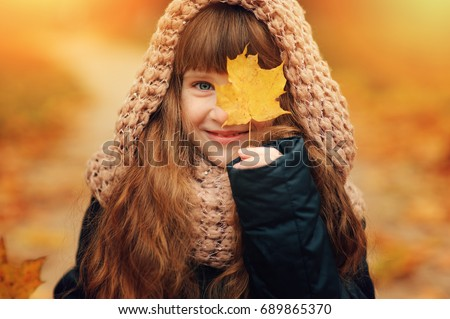 Stock Photo autumn outdoor portrait of beautiful happy child girl walking in park or forest in warm knitted scarf