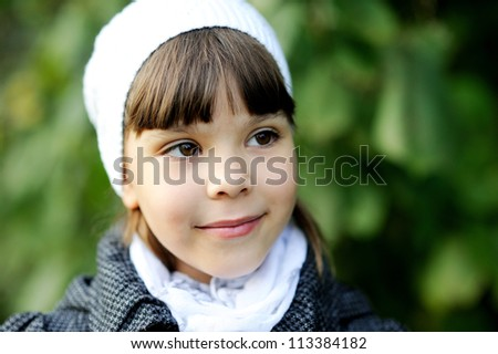 Autumn outdoor portrait of little girl wearing white hat