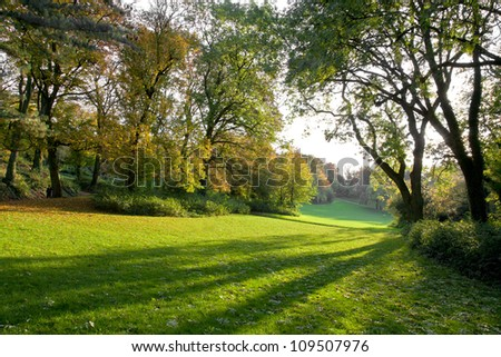 Autumn Park at sunset. The shadows on the green grass lawn. Autumn landscape.