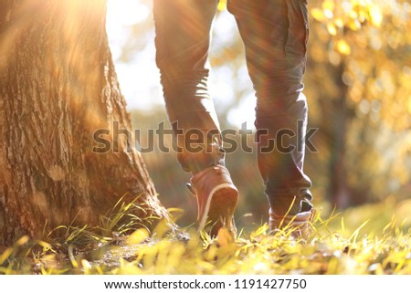 Autumn Park man walking along a path foliage #1191427750