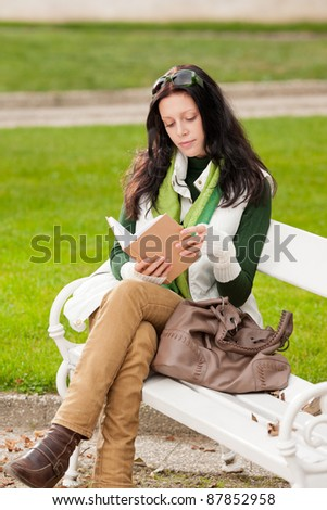 Autumn park young woman reading book sitting on the bench