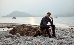 Autumn photo of young fashionable male model wear turtleneck and posing outdoor near the lake