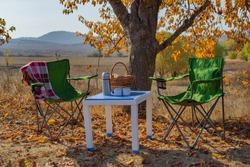 Autumn picnic in the mountains, warm autumn day. Basket with food on the table. Herbal tea, thermos on the background of autumn forest and mountains. Beautiful tree in yellow foliage. Autumn concept.