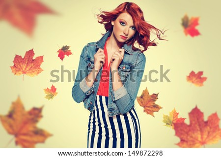 autumn picture of young beautiful red haired girl with maple leaves. red hair. studio