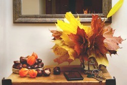 Autumn plant decorations in interior. Bouquet of maple leaves, chestnuts and chinese lantern plants on table in entryway.