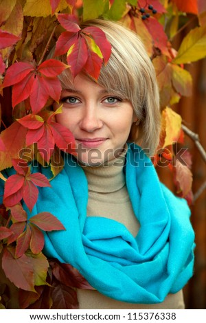 Autumn portrait a lovely young gray-eyed blond woman. A beautiful face is framed by bright colorful autumn leaves.