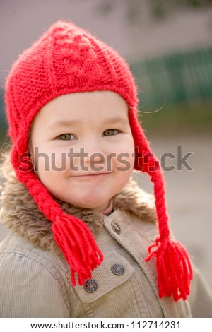 Autumn portrait of a beautiful little girl wearing a red hand knitted hat with braids. Smiling face closeup