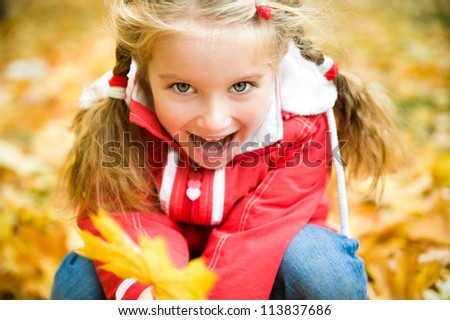 Autumn portrait of a pretty little girl