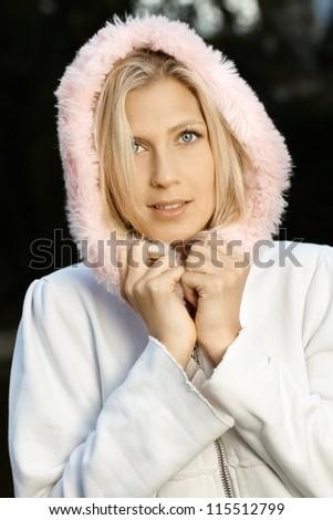 Autumn portrait of attractive blonde girl wearing hood.