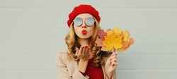 Autumn portrait of beautiful young woman model with yellow maple leaves blowing her lips with lipstick wearing a red french beret on gray background