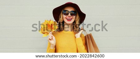 Autumn portrait of happy smiling young woman with shopping bags and yellow maple leaves wearing a sweater and hat on gray background