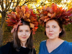 Autumn portrait of smiling mother and daughter with wreaths woven from maple leaves on heads,against yellowing nature.Concept of generational continuity,imperfection,happy parent-child relationships.