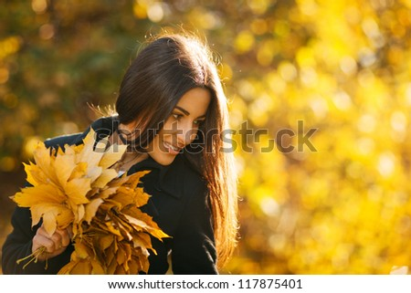 Autumn portrait of young woman in fall colors outdoors holding a bunch of yellow maple leaves