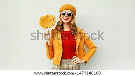 Autumn portrait smiling woman holding yellow maple leaves wearing french beret posing on city street over gray wall background