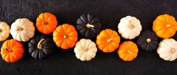 Autumn pumpkin banner Halloween colors orange, black and white against a black stone background