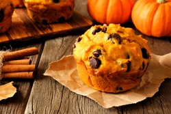 Autumn pumpkin chocolate chip muffin. Close up table scene on a rustic wood background.