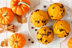 Autumn pumpkin chocolate chip muffins. Top view table scene on a bright white wood background.