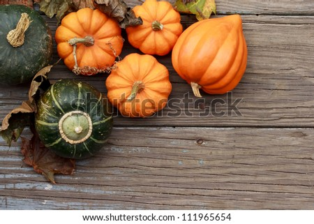 Autumn pumpkins with leaves  on wooden board #111965654