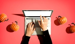 Autumn pumpkins with person using a laptop computer from above
