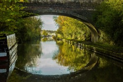 Autumn reflections of Wolfhamcote Bridge No 98, narrowboats, autumn leaves, colors, Oxford Canal near Wolverton, England.  Peaceful autumn light. Picturesque, scenic. Canal life.  Destination holiday.