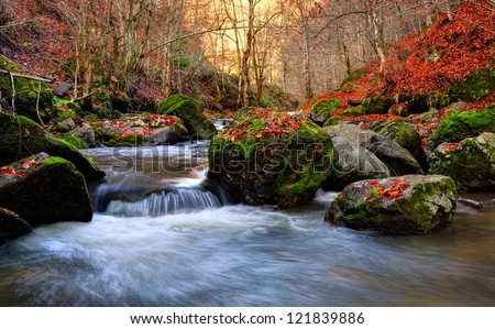 Autumn river cascade with sunlight in background