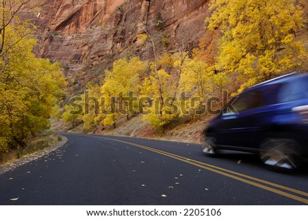 Autumn road in Zion National Park, Utah. Yellow foliage, red rocks and a motion-blurred blue car zooming by...