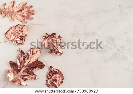 Autumn rose gold colored leaves, creative flatlay on white marble background. Copy space for text