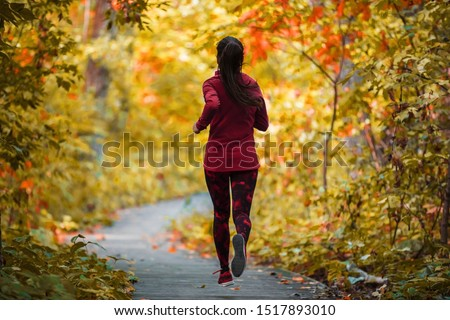 Autumn run active fit runner woman jogging in foliage forest woods of park, healthy living lifestyle exercising cardio in fresh air of outdoors.