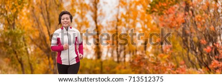 Autumn running middle age Asian woman jogging in park banner panorama. Active lifestyle mature lady in her 50s living a healthy life. #713512375