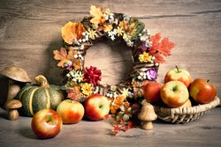 Autumn rustic decorations, floral wreath and apple basket. Natural Fall Thanksgiving harvest. Autumn leaves, decorative wreath, berry and wooden mushrooms. Eco friendly zero waste decor.