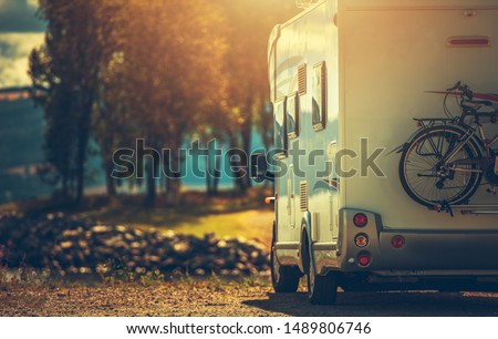 Autumn RV Camping. Modern Camper Van During Late Sunny Fall Afternoon. Scenic RV Park.