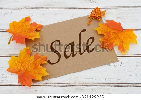 Autumn Sale Card, A brown card with words Autumn Sale over a distressed wood background with Autumn Leaves