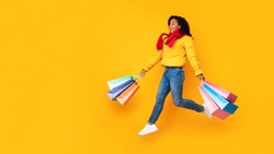 Autumn Sales. African Shopaholic Woman Holding Shopping Bags Running In Mid-Air Wearing Winter Clothes On Yellow Studio Background. Panorama, Copyspace