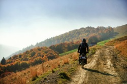 Autumn scene with a motorcycle on a mountain dirt road at golden hour