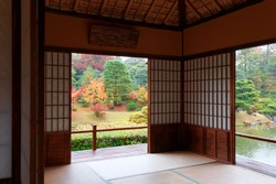 Autumn scenery of colorful foliage in a Japanese garden in beautiful Katsura Imperial Villa, Kyoto Japan, with a view thru the sliding screen doors (Shoji) of a tea room in a peaceful Zen ambiance