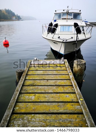 Autumn seascape. Old wooden pier covered with moss and a white boat moored at the shore. Peaceful autumn scandinavian scenery: bay of the sea with calm water, fog, Islands, rocky shores and pine trees #1466798033