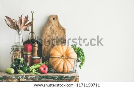 Autumn seasonal food ingredients, kitchen utensils. Vegetables, pumpkin, apples, canned food, fallen leaves over rustic wooden chest of cupboard, copy space. Thanksgiving dinner preparation