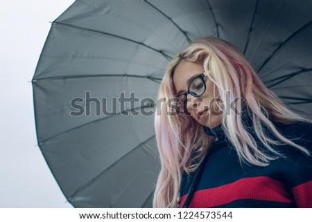 autumn seasonal sadness emotions under umbrella in gray rainy day time, Caucasian Ukrainian girl portrait without make up