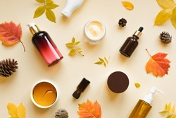 Autumn Skin Care products and autumn leaves on yellow background, flat lay, copy space.  Seasonal beauty routine and organic cosmetic concept.