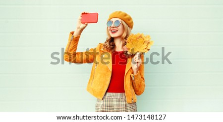 Autumn smiling woman taking selfie picture by phone holding yellow maple leaves wearing french beret hat posing on city street over gray wall background